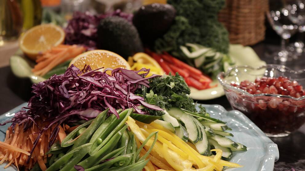 Strimlade grönsaker av all de slag i en färgrik mix på tallrik.