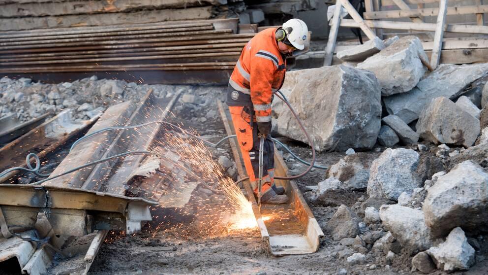 En byggarbetare med skärbrännare arbetar vid ombyggnaden av Slussen i Stockholm.