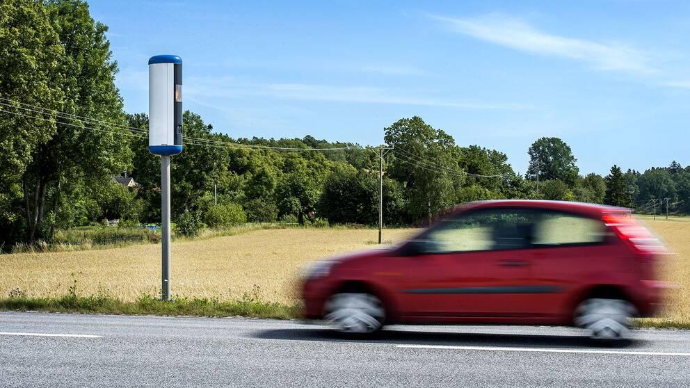 fartkamera framför åker med träd i bakgrunden och en röd framfarande bil i oskärpa