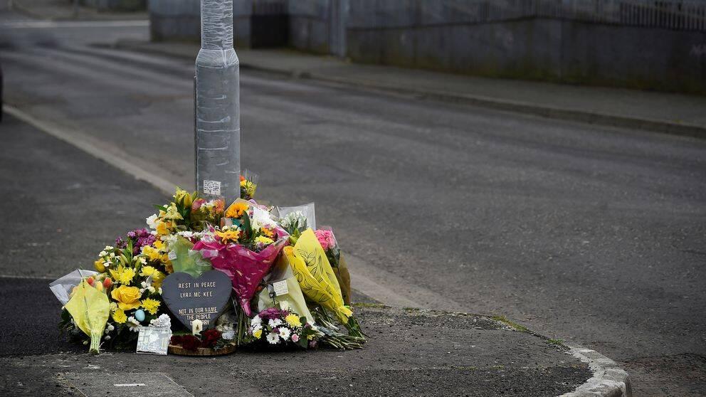Blommor på asfalterad gata vid en lyktstolpe.