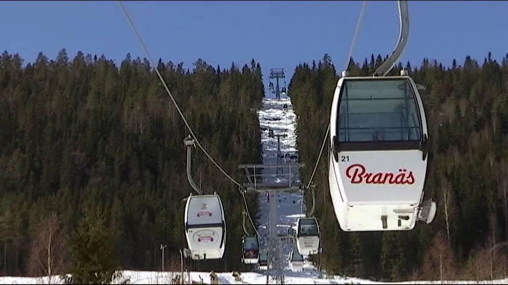 En kabinlift som det står Branäs på. I bakgrunden gröna granar och på marken vit snö.
