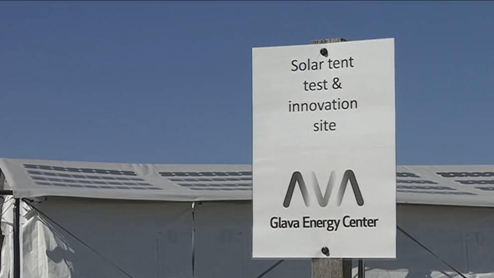 """Vit skylt framför solcellstält med texten """"Solar tent test & innovation site"""""""