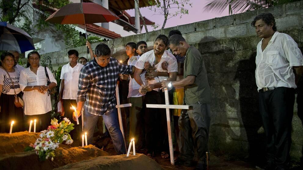 Släktingar lägger blommor efter begravningen av tre som dog St. Sebastian-kyrkan.