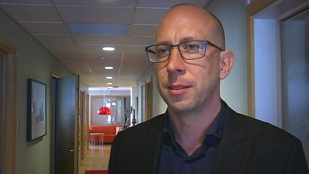 Magnus Andersson, kommunstyrelsens ordförande i Hallsberg, står i en korridor med ljusa väggar.