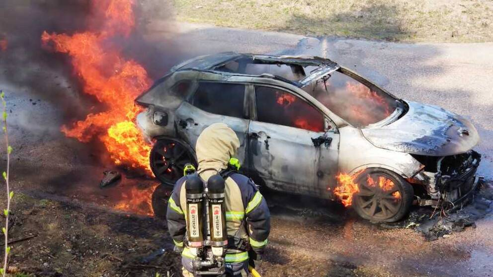 Brandman som står framför bil som brinner för fullt.