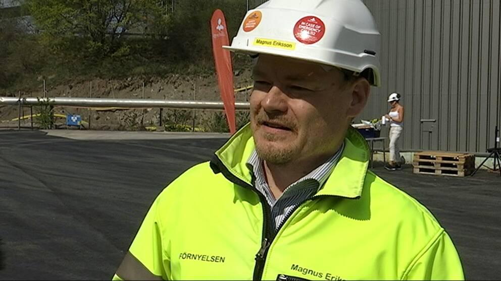 Magnus Eriksson är värmechef på Mälarenergi. Här står han framför den nya ackumulatortanken som syns vid kraftvärmeverket i Västerås.