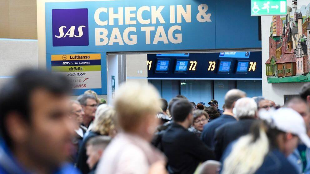 Passagerare på Arlanda flygplats framför SAS-incheckning.