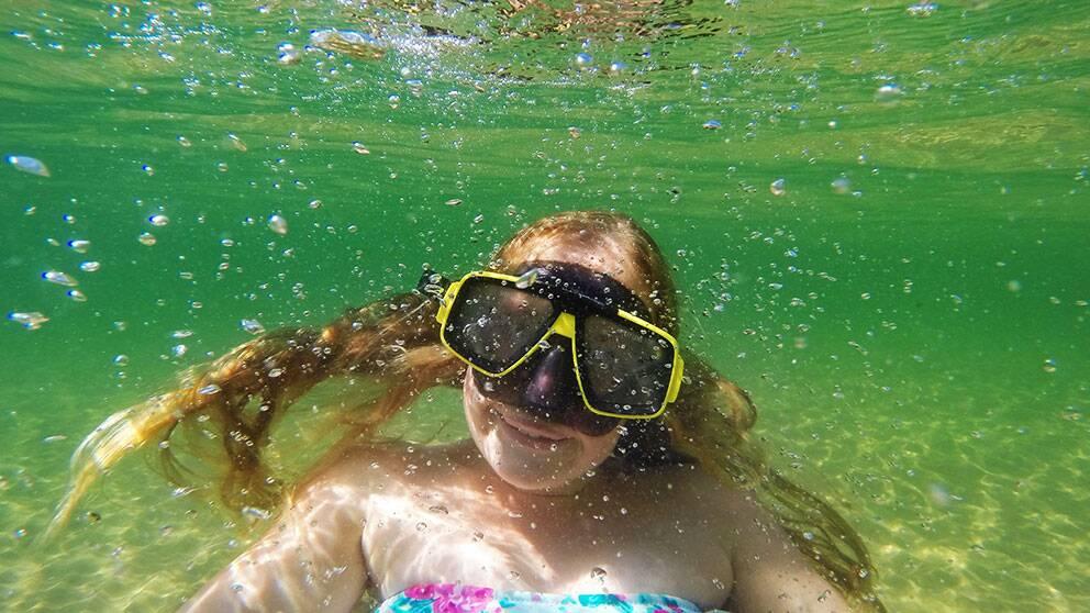 Flicka i cyklop simmar under vattnet i Vättern.