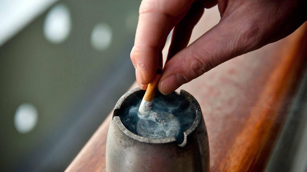 närbild hand som fimpar en cigarett i askkopp
