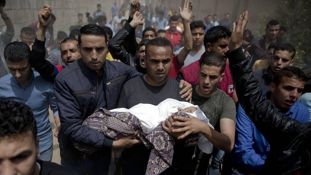 Palestinier sörjer det 14-månader gamla barn som dödats i Gaza.