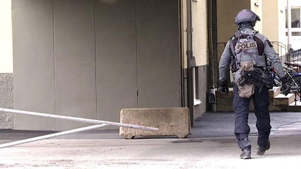 en polis i insats-utrustning går förbi en husknut