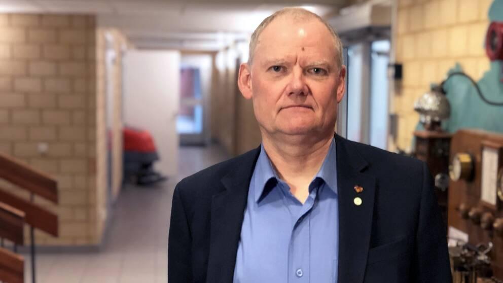 Porträttfoto av Bengt Friberg. Han står bredvid en trappa och en korridor syns i bakgrunden.