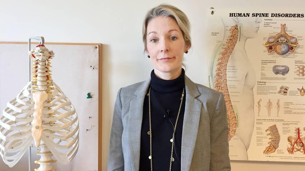 Sandra Schönbeck bredvid ett skelett och en plansch om ryggskador.