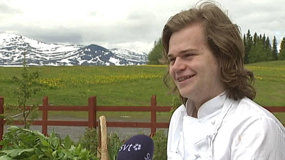 en ung man intervjuas framför vy över grön äng och snöigt fjäll