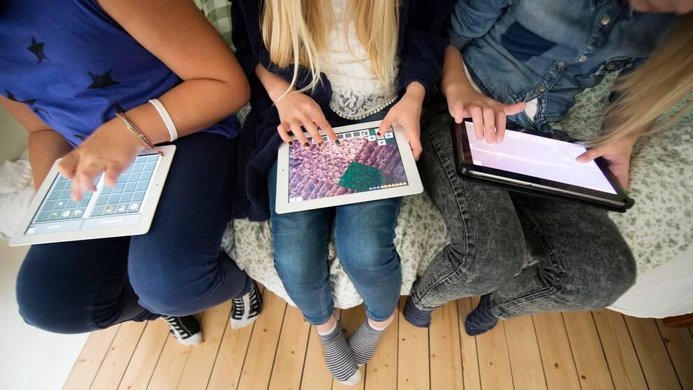Tre flickor spelar datorspelet Minecraft online på sina surfplattor.