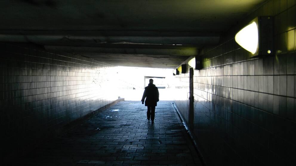 En människa går genom en mörk tunnel.