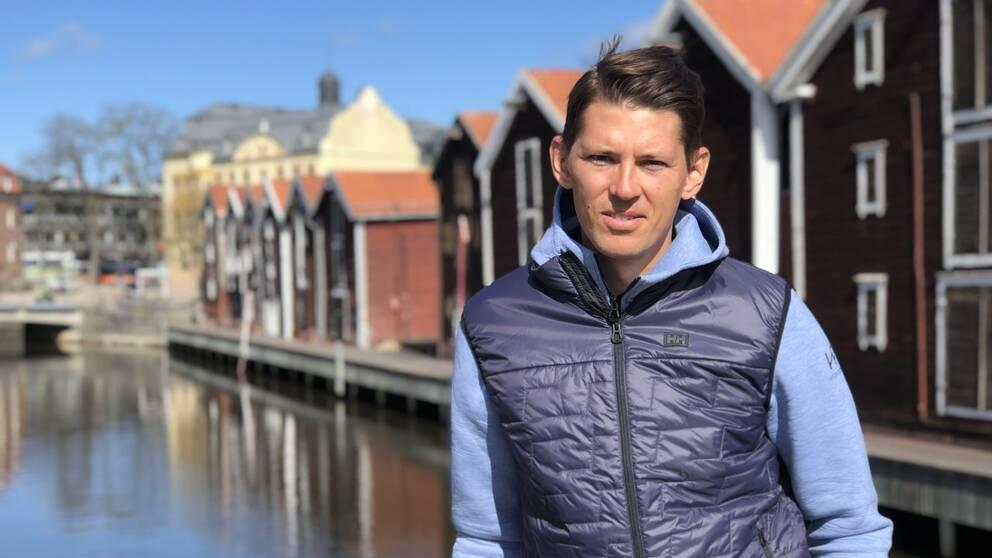 Porträttfoto av André Myhrer. I bakgrunden syns flera träbyggnader och en vattenansamling.
