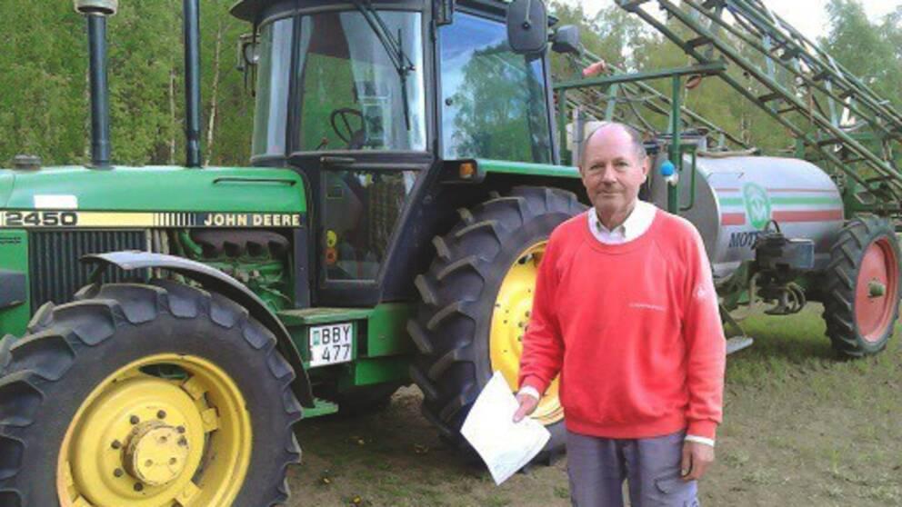 Kent Eriksson framför sina gröna traktor