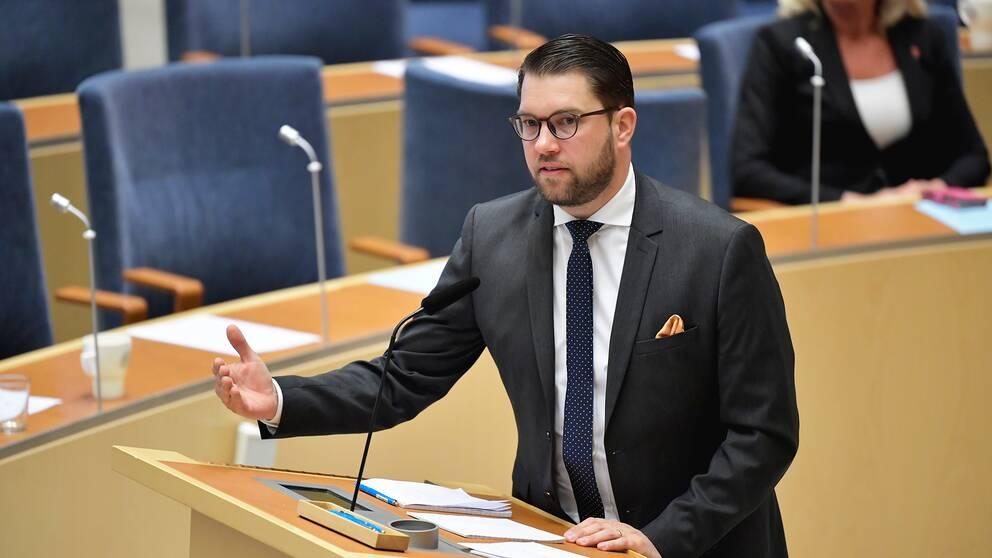 Sverigedemokraternas partiledare Jimmie Åkesson står vid en talarstol och pratar under riksdagsdebatten.