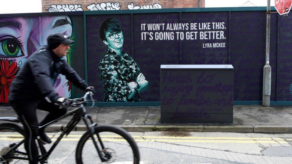Cyklist passerar en väggmålning utomhus, på väggen syns en bild av den mördade journalisten Lyra McKee.