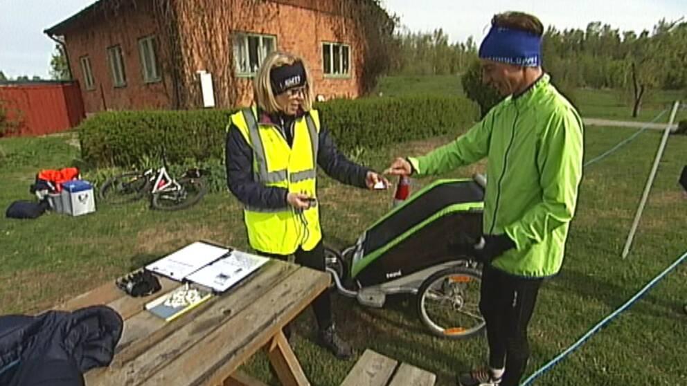 Volonär i Örebro tar emot löpare (med barnvagn) som kommit i mål och registrerar tiden.