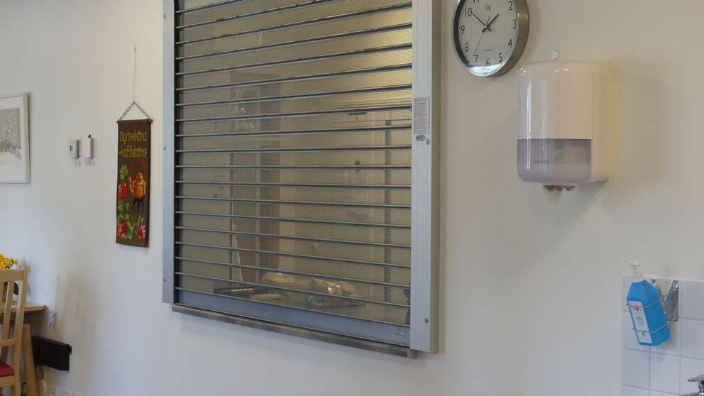 På bilden syns avdelningsköket bakom en gallerliknande jalusi. På väggen intill finns en bonad, en klocka och en flaska med desinfektionsmedel.