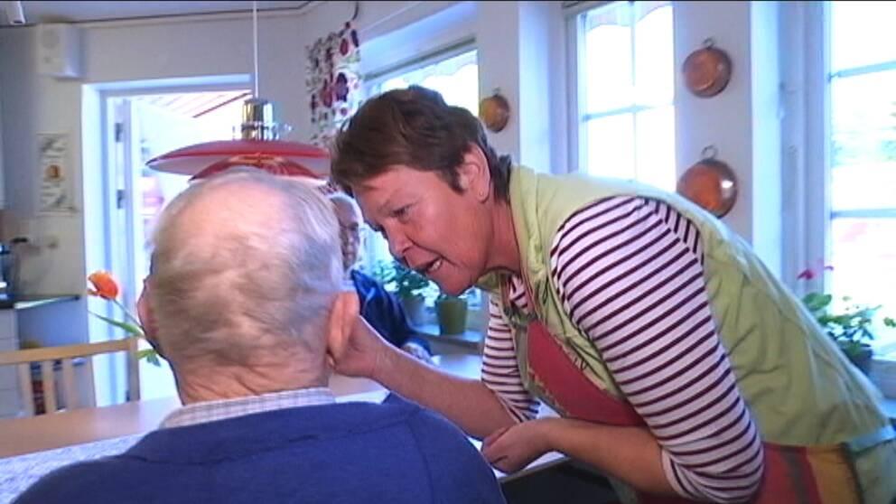 Kökspersonalen stoppar in i en sked i munnen på en äldre man som får smaka av maten som lagas.