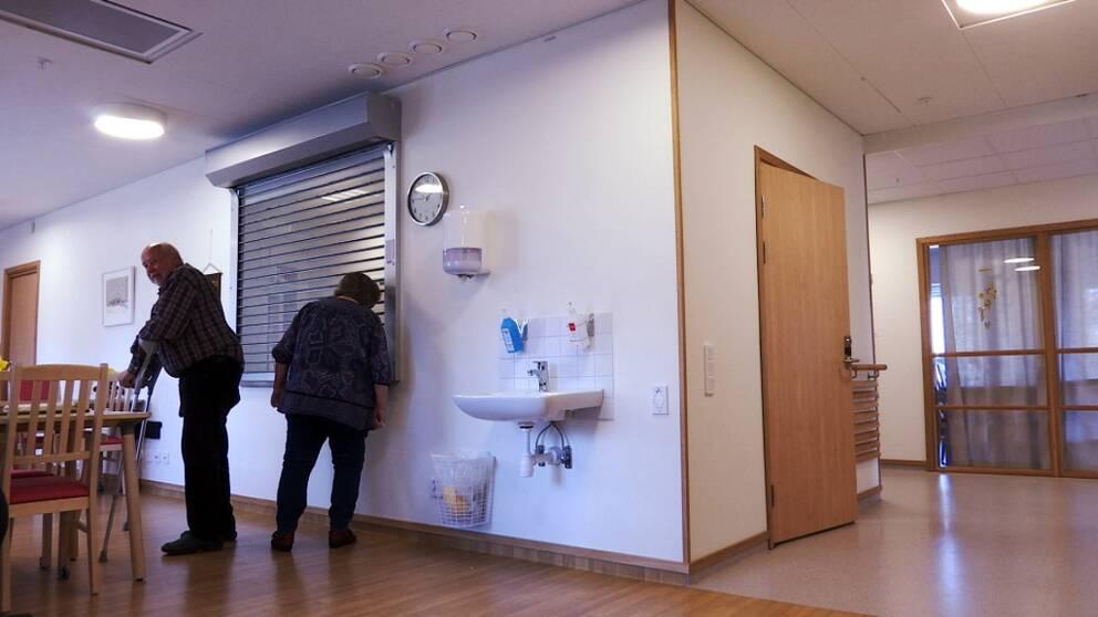 På bilden syns en vägg med en lucka där en gallerliknande jalusi har dragits ner. En kvinna tittar in genom gallret där det gemensamma avdelningsköket finns.