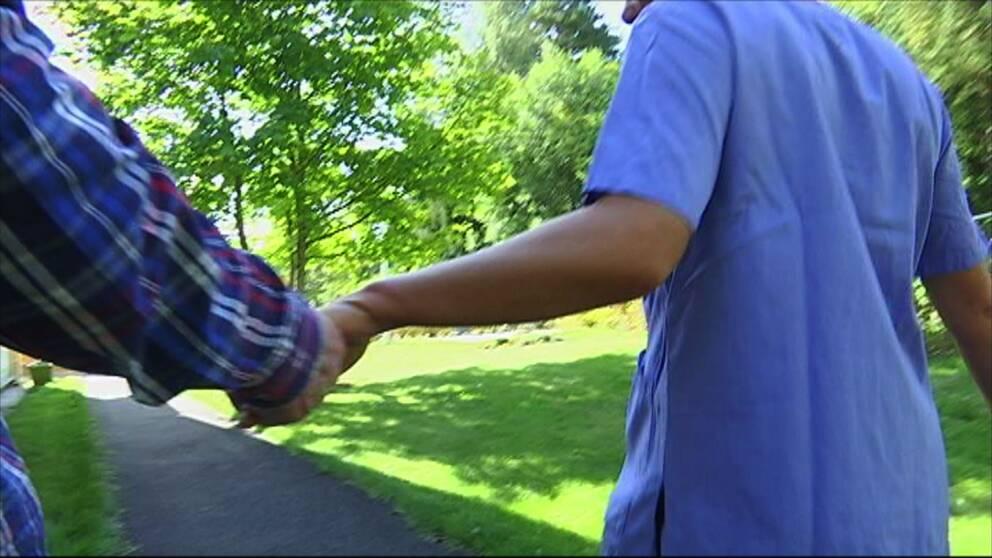 En man håller handen på en undersköterska.