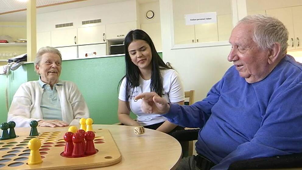 Två äldre personer spelar fia med knuff tillsammans med en yngre tjej.