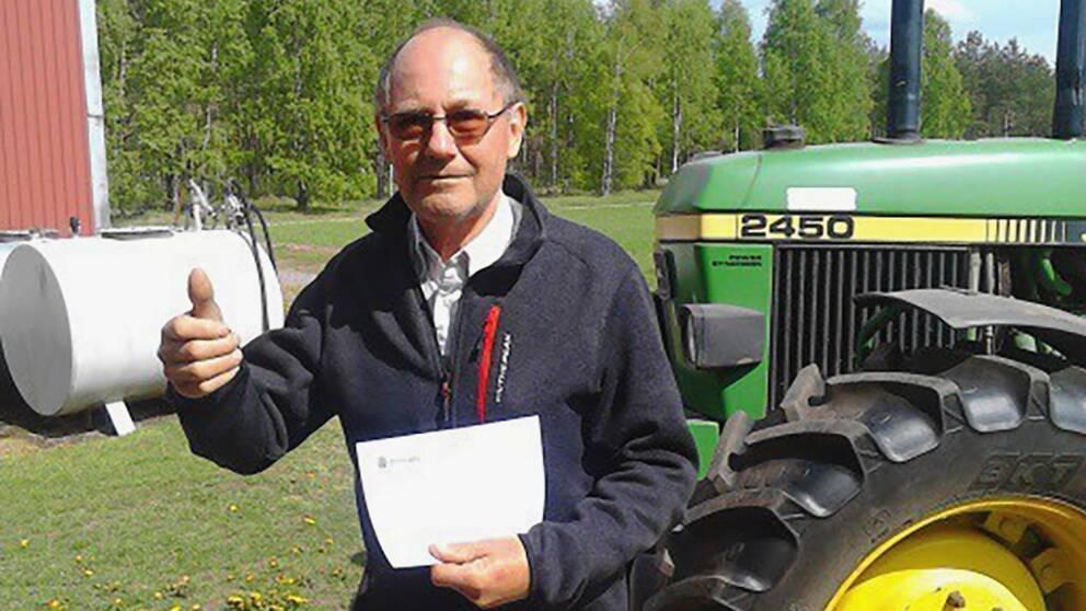 Kent Eriksson med brevet som visar att parkeringsboten och traktorn bakgrunden