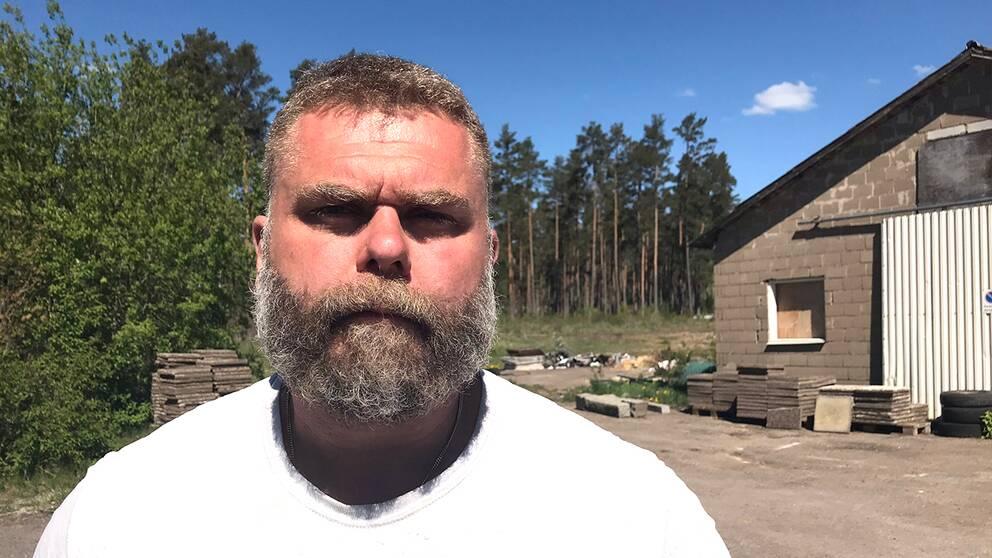 En man med stort skägg och alvarlig min står framför ett hus