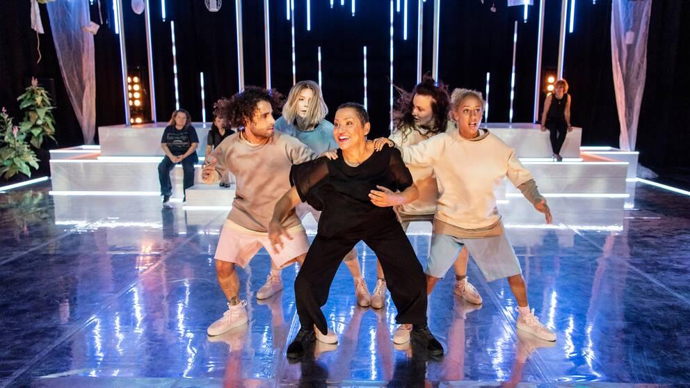 I bilden syns fyra dansare och en mamma uppträda på scenen.