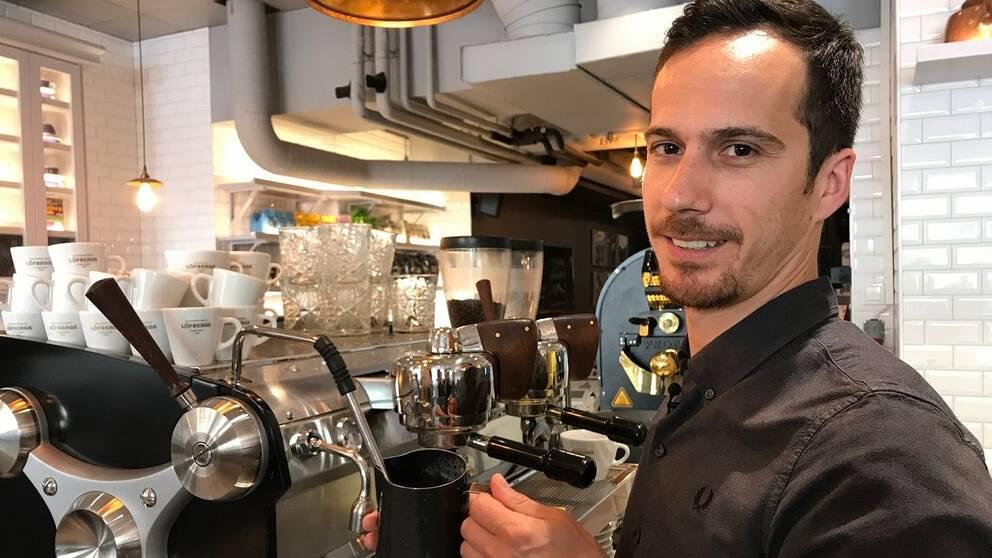 Alex Ntatsos håller i en kanna med kaffe framför en kaffemaskin