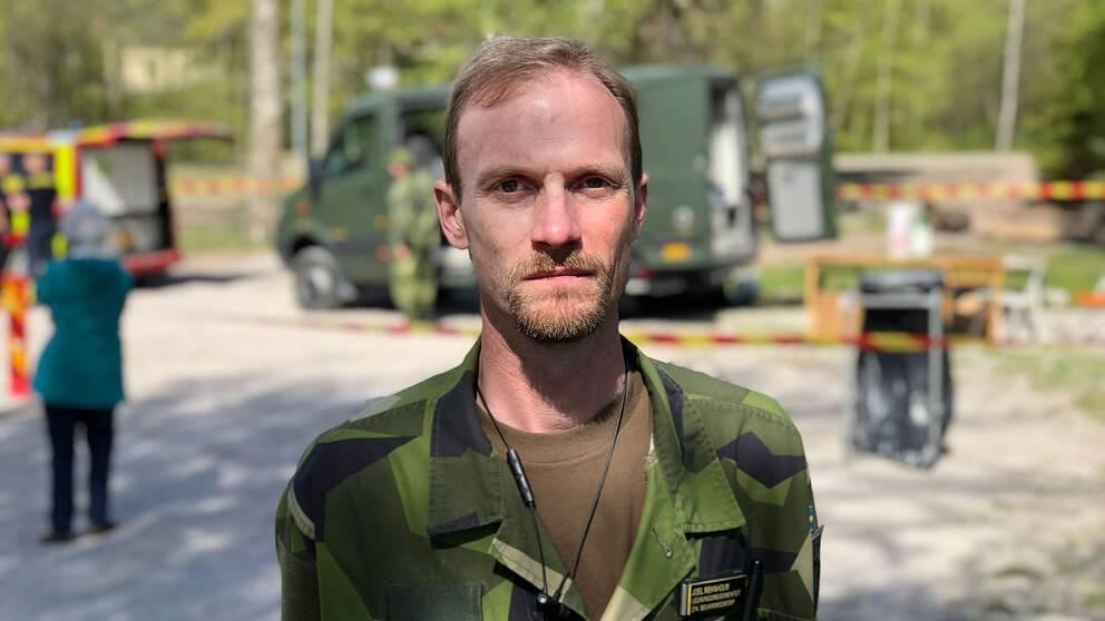 Joel Rehnholm framför ett av Hemvärnets fordon. I bakgrunden syns räddningstjänstens avspärrningar.