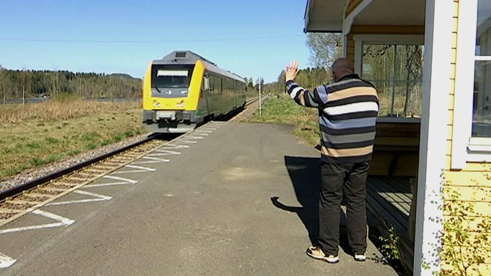 Äldre man vinkar åt ett förbipasserande tåg vid Oleby station.