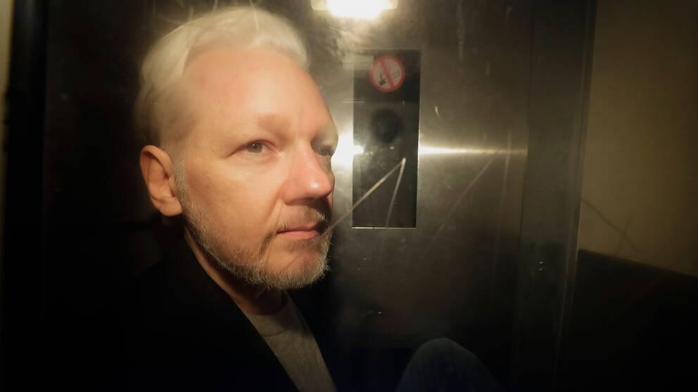 Julian Assange fotograferad genom rutan på en bil utanför domstolen i London.