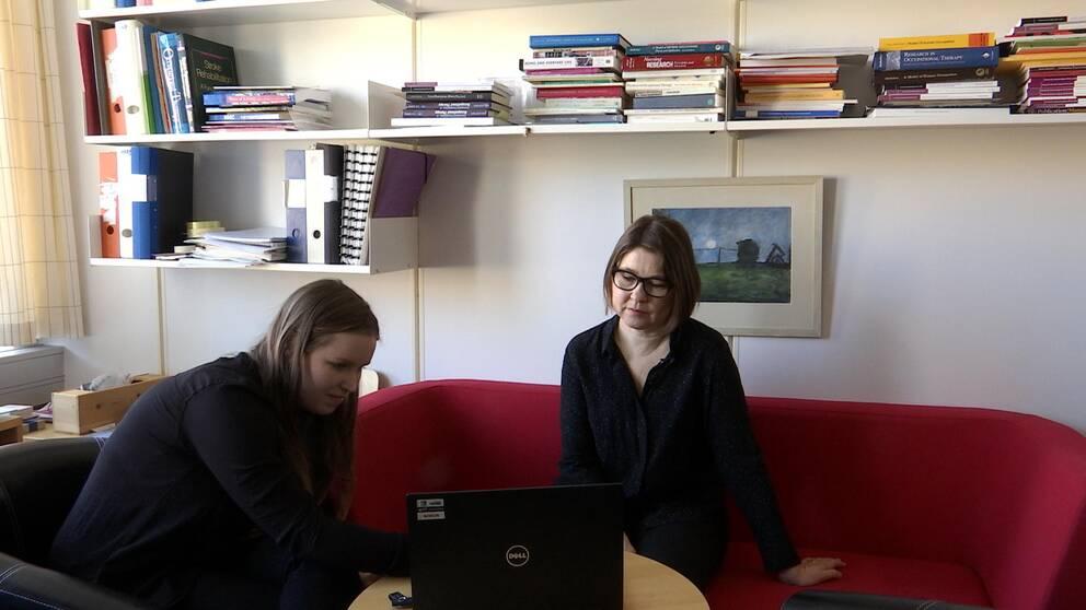 En bild på reportern som visar ett reportage för en forskare. De sitter på ett kontor med en röd soffa.