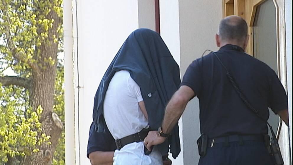 En misstänkt person leds in i en tingsrättsbyggnad av två andra personer. Den misstänkte har en jacka över huvudet.
