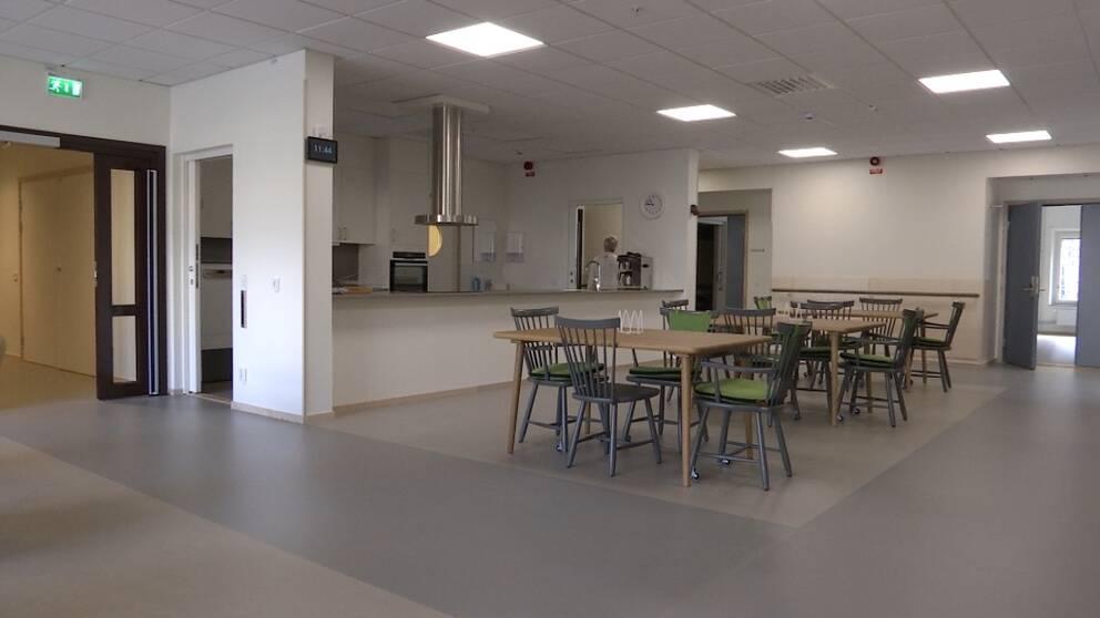En stor matsal med ett kök som har en lång disk där man kan stå på båda sidor om disken och laga mat.