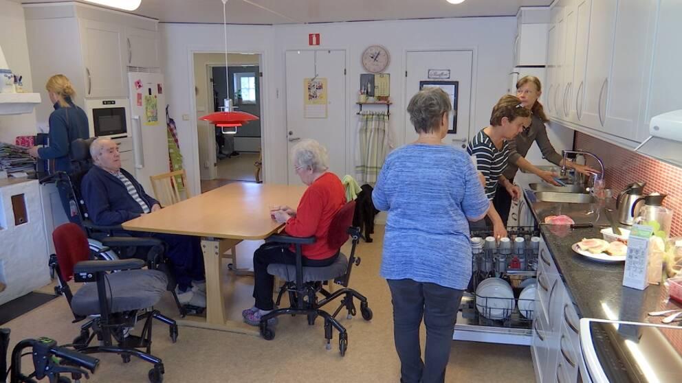 De äldre sitter vid ett bord mitt i köket medan personalen fixar i köket.