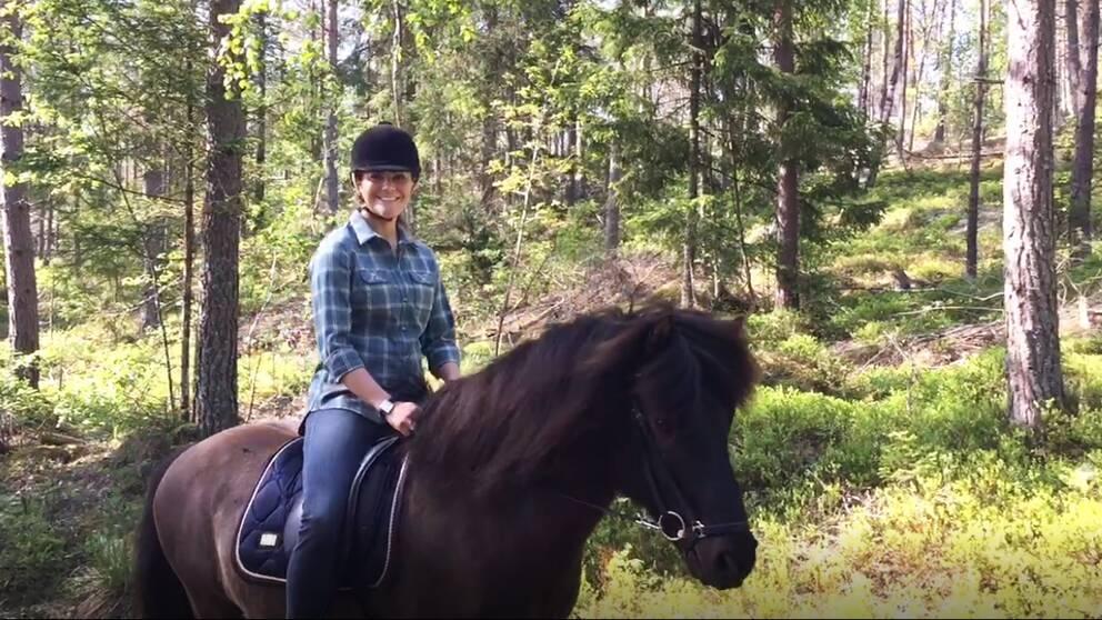 Kronprinsessan Victoria rider in i Sörmland på ryggen på en mörkbrun islandshäst. Hon ser glad ut, är iklädd rutig skjorta och ridhjälm.