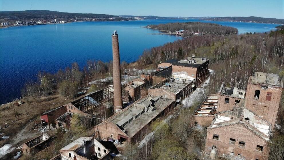 flygbild över fabriksruiner – tegelbyggnader och skorsten invid vatten