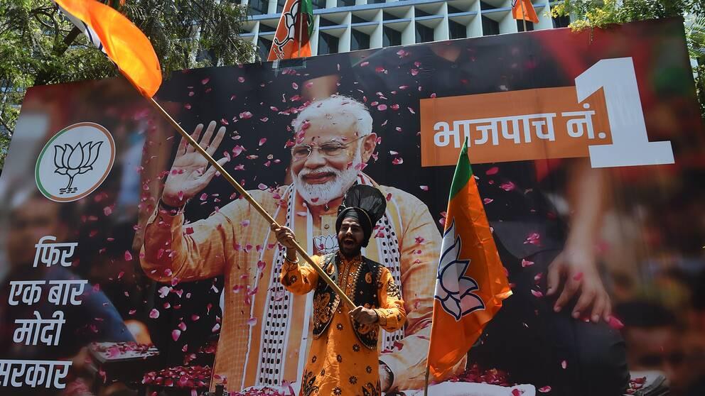 En man viftar glatt med en orange flagga framför en stor bild på indiske premiärministern Narendra Modi.