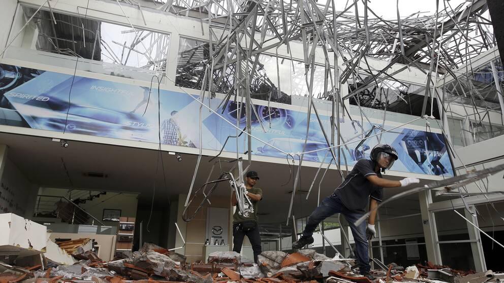 Två män röjer bråte efter en jordbävning.