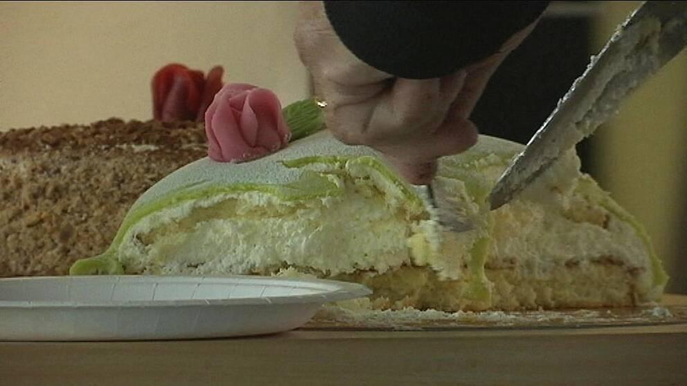 tät bild på prinsesstårta och en person som skär en bit