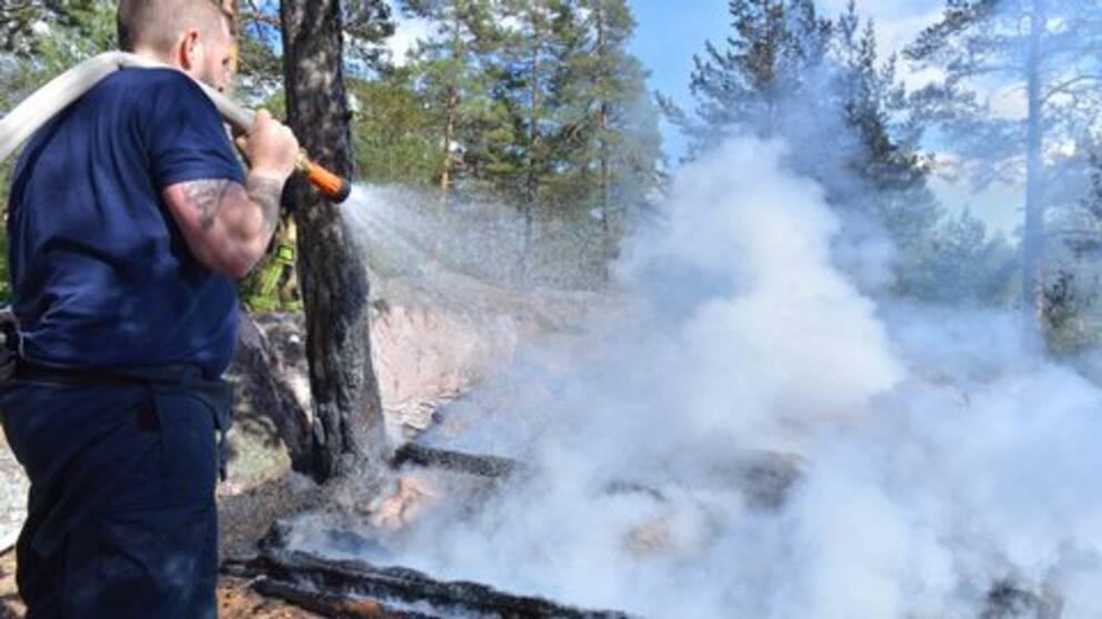 Brandman släcker elden i vindskydden.