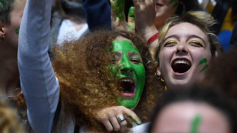 Två tjejer med ansiktsmålning strejk för klimatet i Paris.