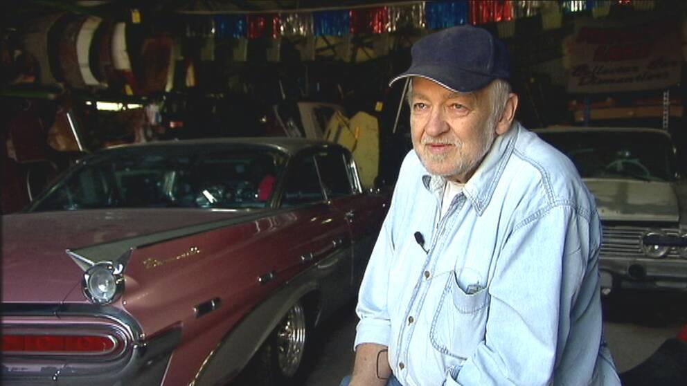 Man med keps sitter framför en veteranbil.
