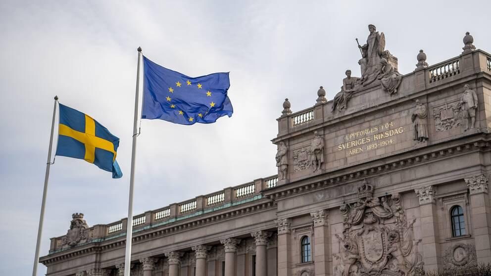Sveriges och EU:s flaggor hissade framför Riksdagshuset i Stockholm.